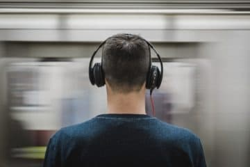 Man in a train station listening to loud music
