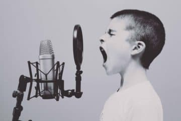 Young boy screaming into a microphone simbolizing loud noise