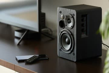 Speaker with remote control making a hissing sound on a TV stand