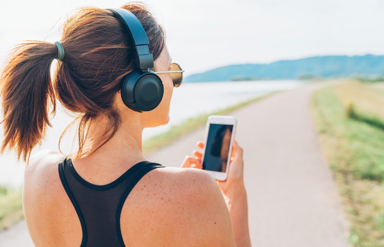 Woman listening to music while running a marathon she's using her headphones