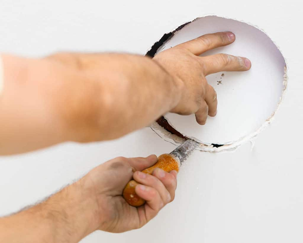 Cutting the drywall to install an in-ceiling speaker backbox