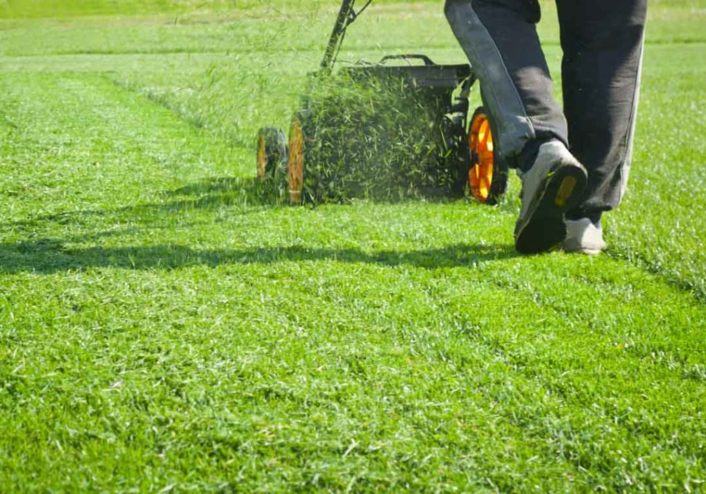 Is it safe to wear headphones while mowing the lawn