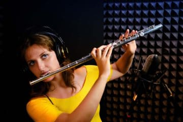 How Do You Record a Flute Solo? The flute might be famous for solos thanks to movies like Anchorman: The Legend of Ron Burgundy, but it isn't an easy instrument to record. Flutists produce unique sounds that can create some unfamiliar challenges for audio engineers. Not only are the notes often hollow and breathy, but they also tend to be quieter than other instruments. Terry Crews might get to play the flute on TV and sound fantastic, but he's got the help of direct audio pickups and filters. What can you do if you're trying to capture sounds with your DAW and home studio equipment? This guide will take you through the process of recording a flute solo accurately and authentically. How Do You Record a Flute Solo? Position the microphone about 12 inches away from the flute to capture its sound accurately. Although there is a small feedback risk, you can take advantage of the proximity to capture beautiful sounds. It helps to have a breathing blocker in place to avoid excessive inhalation sounds when playing. The flute delivers an unmistakable sound when played by an experienced musician. Capturing that audio involves a specific setup when recording. 1. Set the microphone about 8 to 12 inches away from the instrument. When aiming the mic, try to position it about halfway between the left hand and the mouthpiece. Since breathing can be problematic with this setup, it helps to use an omnidirectional design to take advantage of less pop and wind sound. 2. Spot-mic the flute behind and above the player's head. It should point at the finger holes to capture the best sound. 3. Any placement option around the head typically delivers good balance to the instrument's recorded audio, although compact and wide cardioid microphones tend to provide the most consistent performance. You'll reduce mechanical sounds between note changes with this option. Some audio engineers might choose to use directional cardioids instead of wide or omnidirectional ones because they want higher qua
